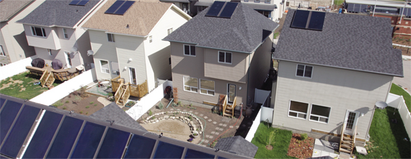 aerial photo of residential houses with solar panels on their roofs.