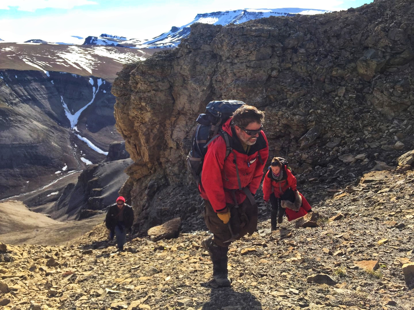 Steve Grasby and team carrying heavy bags of rocks collected from outcrops on northern Ellesmere Island.