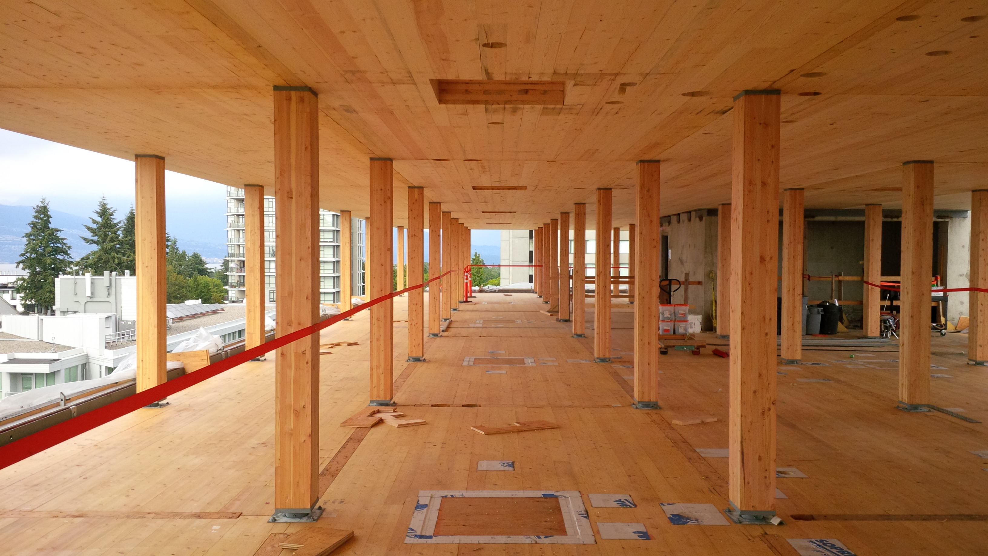 Image of interior of new UBC building under construction showing CLT floor and ceiling, as well as glulam posts