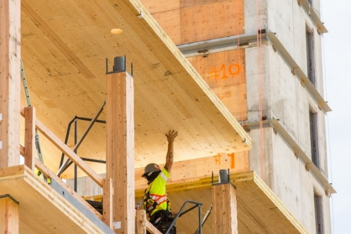 A construction worker helps to assemble engineered mass timber on upper floors of Brock Commons Tallwood House.