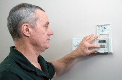 Frank works to program a thermostat.